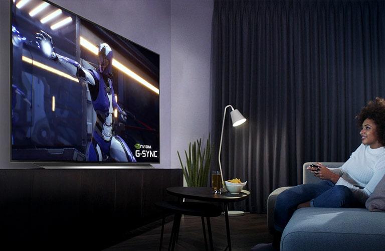 Eine Frau, die auf einem Sofa sitzt und einen Controller hält, während sie ein Spiel auf dem Fernseher spielt