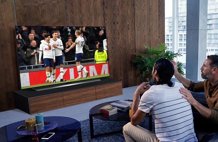 Personen, die sich ein Spiel von Tottenham in ihrem Wohnzimmer auf dem Fernseher ansehen