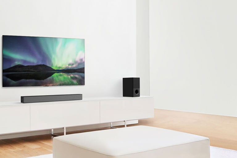 TV and sound bar in white living room with white sofa in the center. Speakers sit on both ends of the sofa.