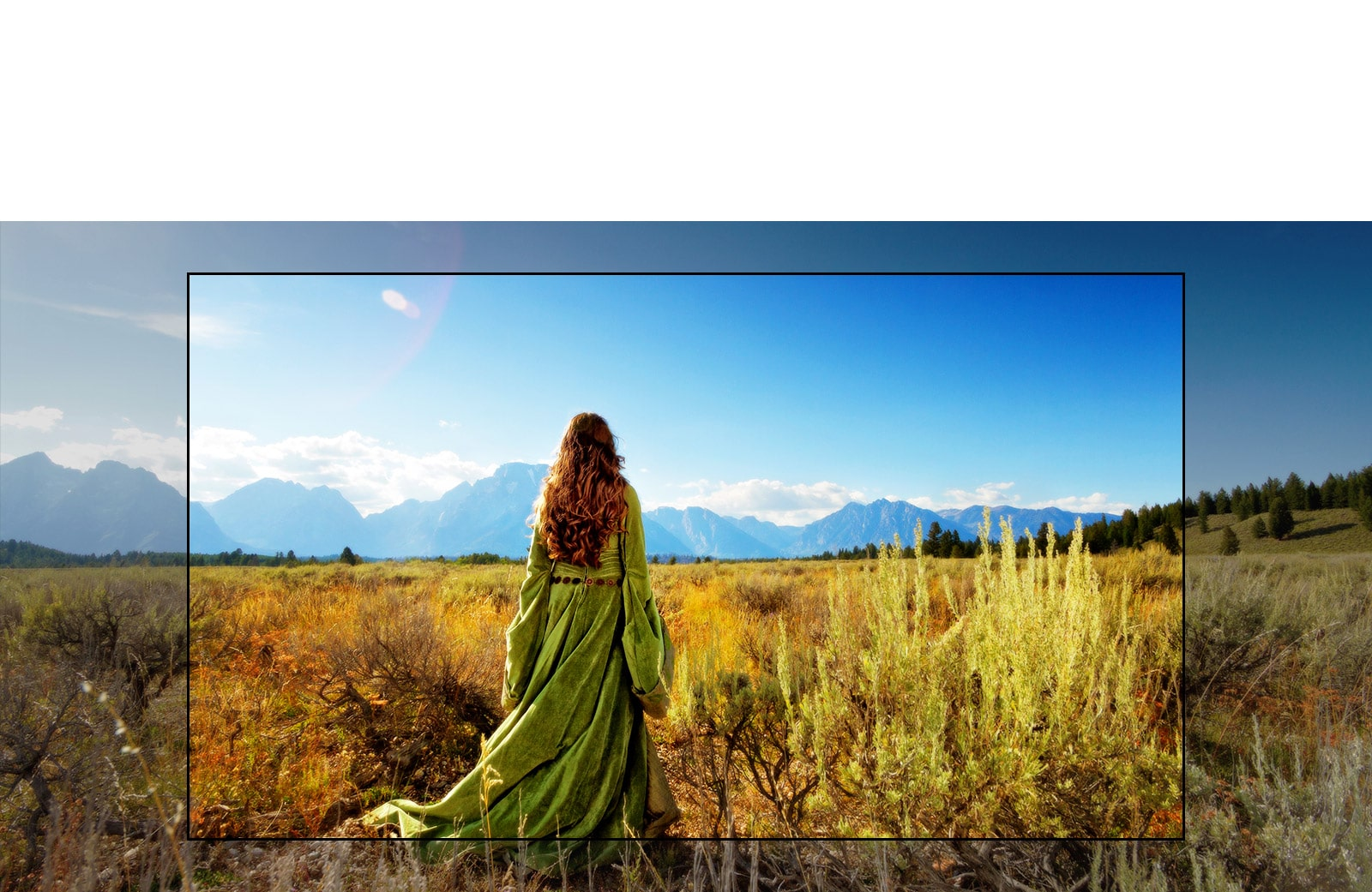 A TV screen showing a scene from a fantasy movie with a woman standing in the fields facing the mountains.