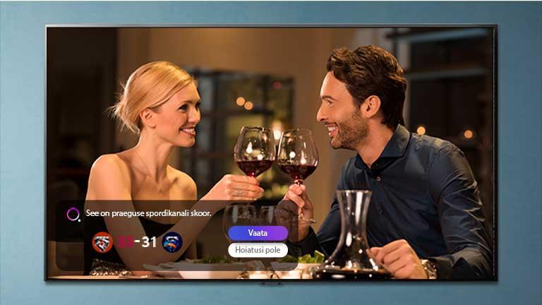 Un barbat si o femeie sparg ochelarii pe un ecran TV, in timp ce rezultatele sportive sunt anuntate
