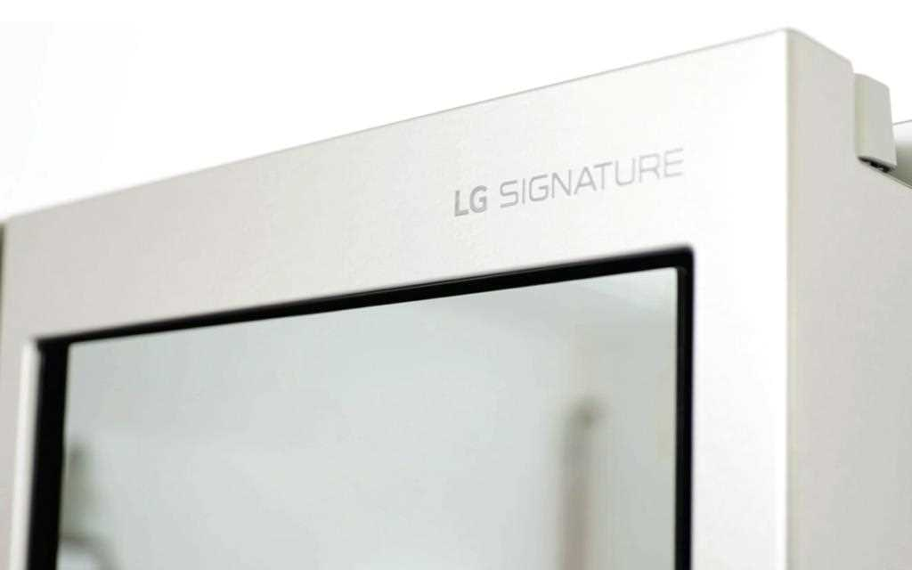 LG SIGNATURE symbol on LG InstaView refrigerator with glimpse of the see-through door