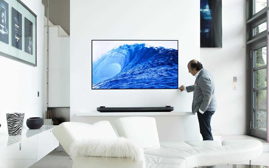 LG W7 OLED TV in an all-white minimalist living room with a man looking at it closely