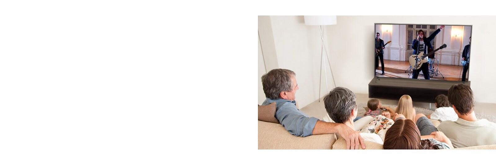 Una familia de siete reunida en el salón y mirando una película. La pantalla del televisor muestra la actuación musical de un grupo.
