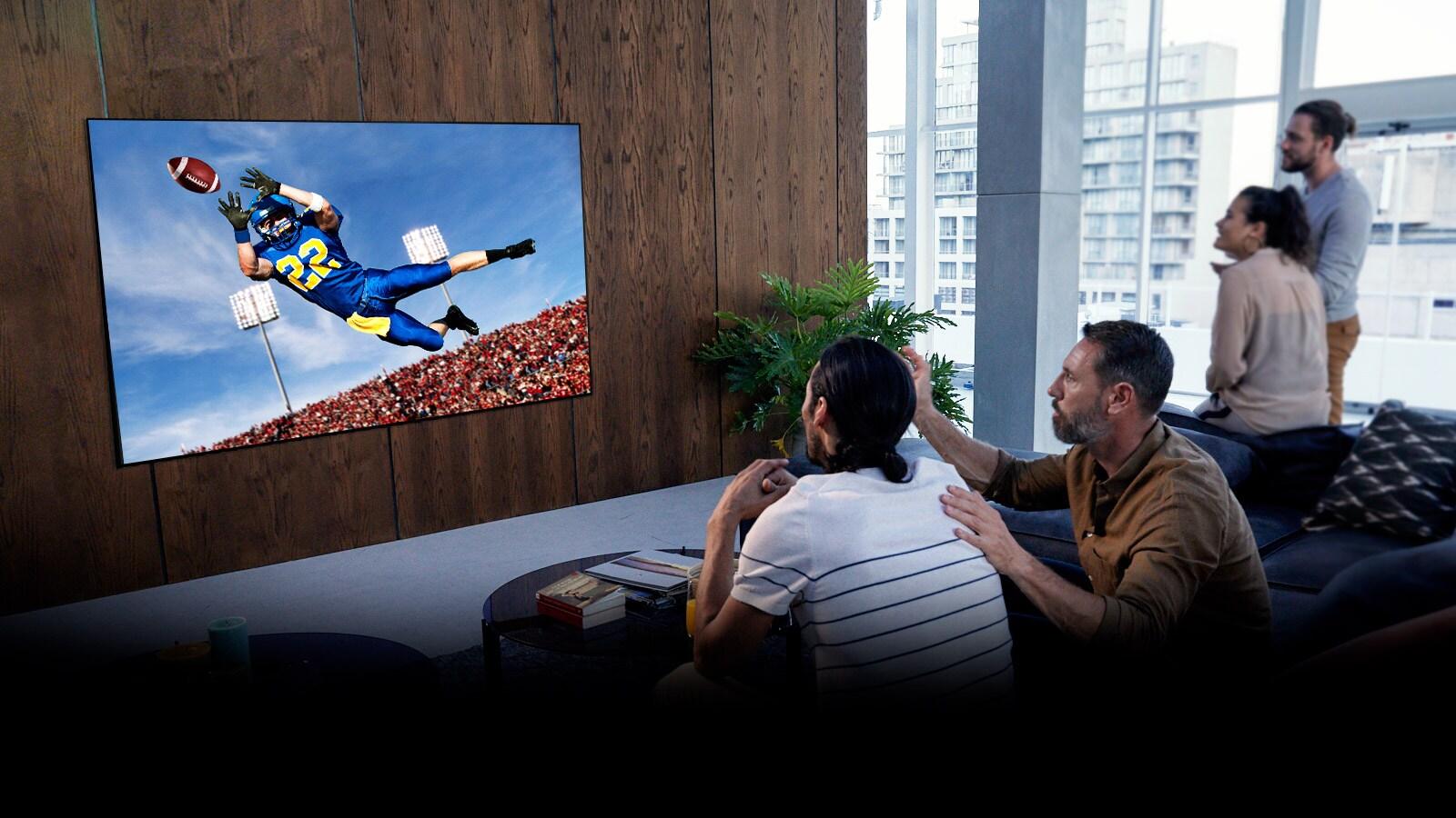 Personas viendo un partido de fútbol americano en la televisión en la sala de estar