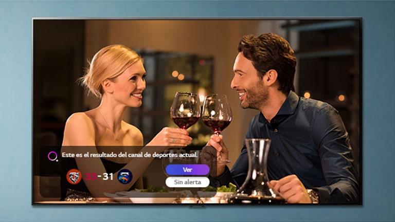 Un hombre y una mujer brindan en una pantalla de TV mientras se notifican las alertas deportivas.