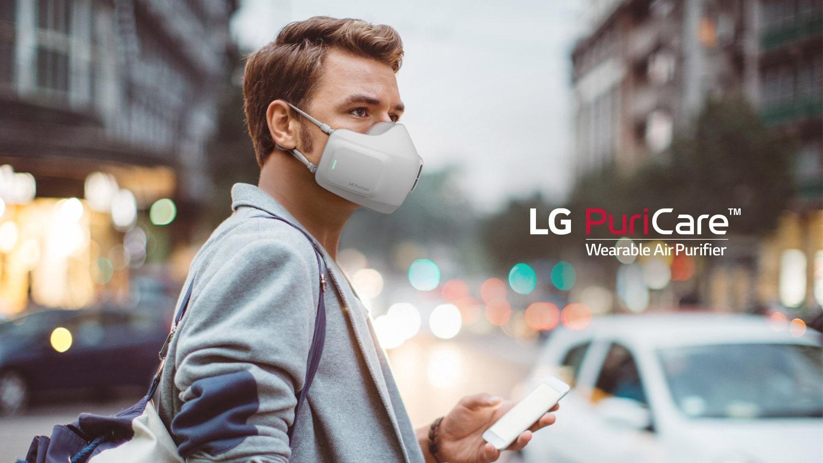 Un hombre está parado en el centro de una ciudad con la máscara LG Puricare puesta, sosteniendo un teléfono y mirando a su alrededor con una ciudad borrosa al fondo.