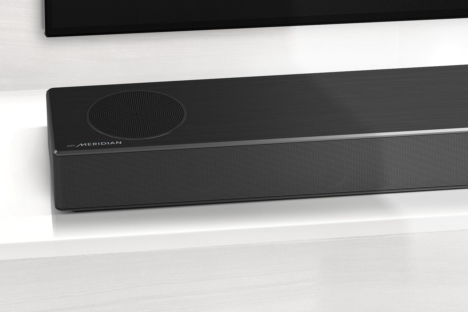 Primer plano del lado izquierdo de la barra de sonido LG con el logo Meridian en la esquina inferior izquierda. También se ve el lado inferior izquierdo del televisor.