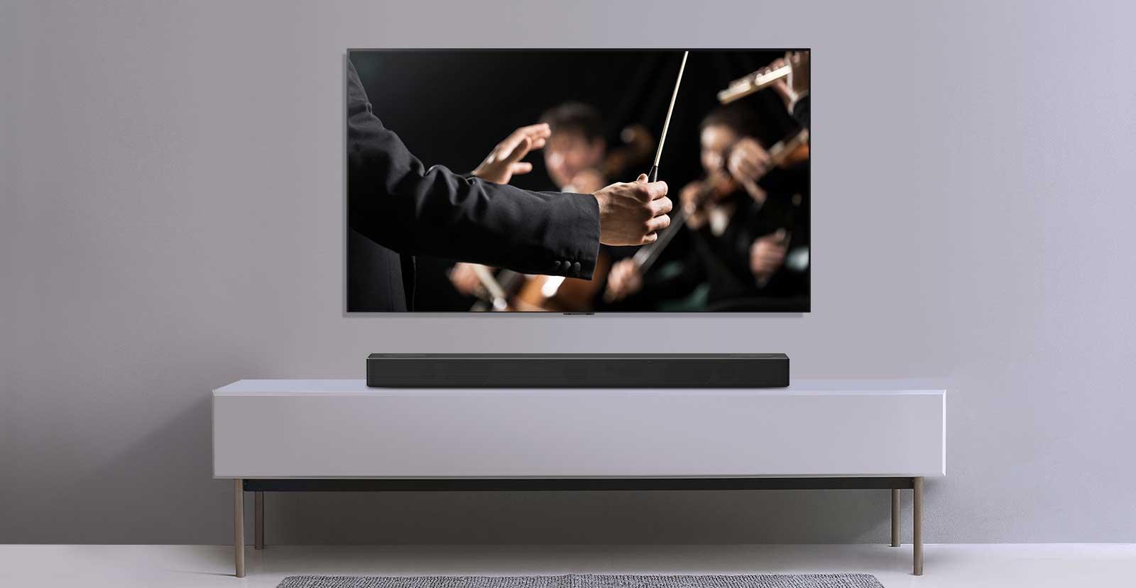 Se muestra un televisor en una pared gris y la barra de sonido LG debajo de un estante gris. El televisor muestra un director dirigiendo una orquesta.