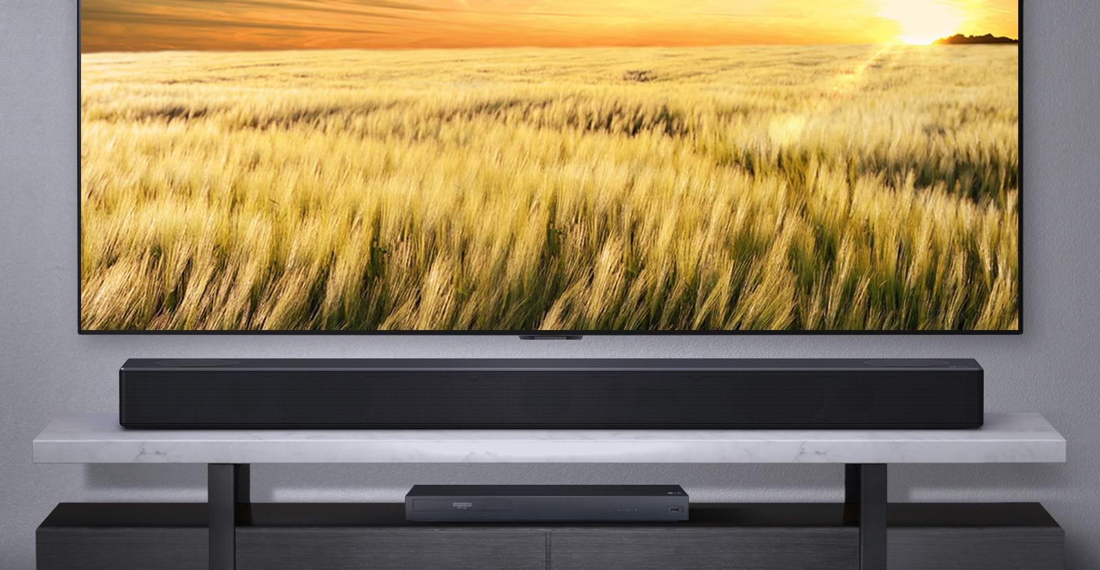 Frontal de la barra de sonido encima del estante con el televisor conectado y el reproductor blue ray