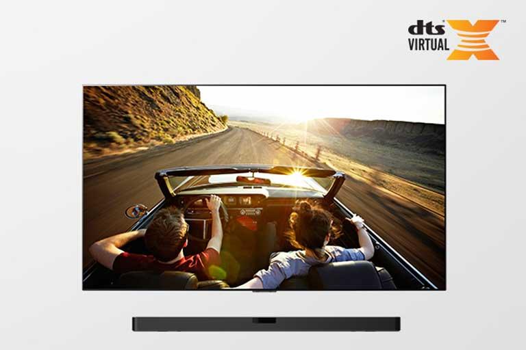 El televisor y la barra de sonido juntos en un plano completo. El televisor muestra una pareja conduciendo un descapotable hacia el crepúsculo.