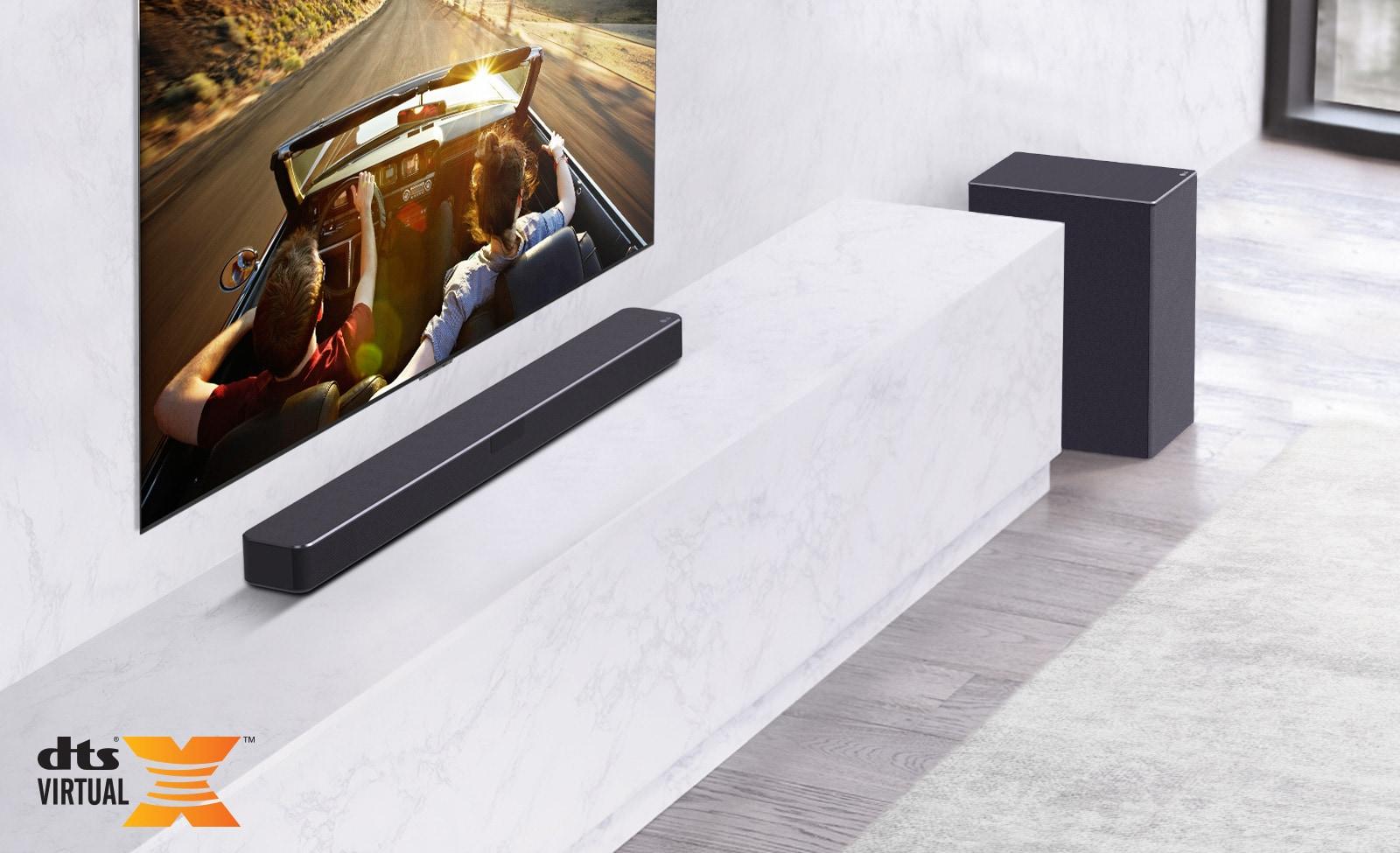El televisor está instalado en la pared, la barra de sonido LG está debajo encima de un estante de mármol blanco con un subwoofer a la derecha. El televisor muestra una pareja en un coche.