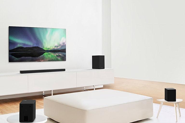 El televisor y la barra de sonido en un salón blanco con un sofá blanco en el centro. Altavoces colocados en ambos extremos del sofá.