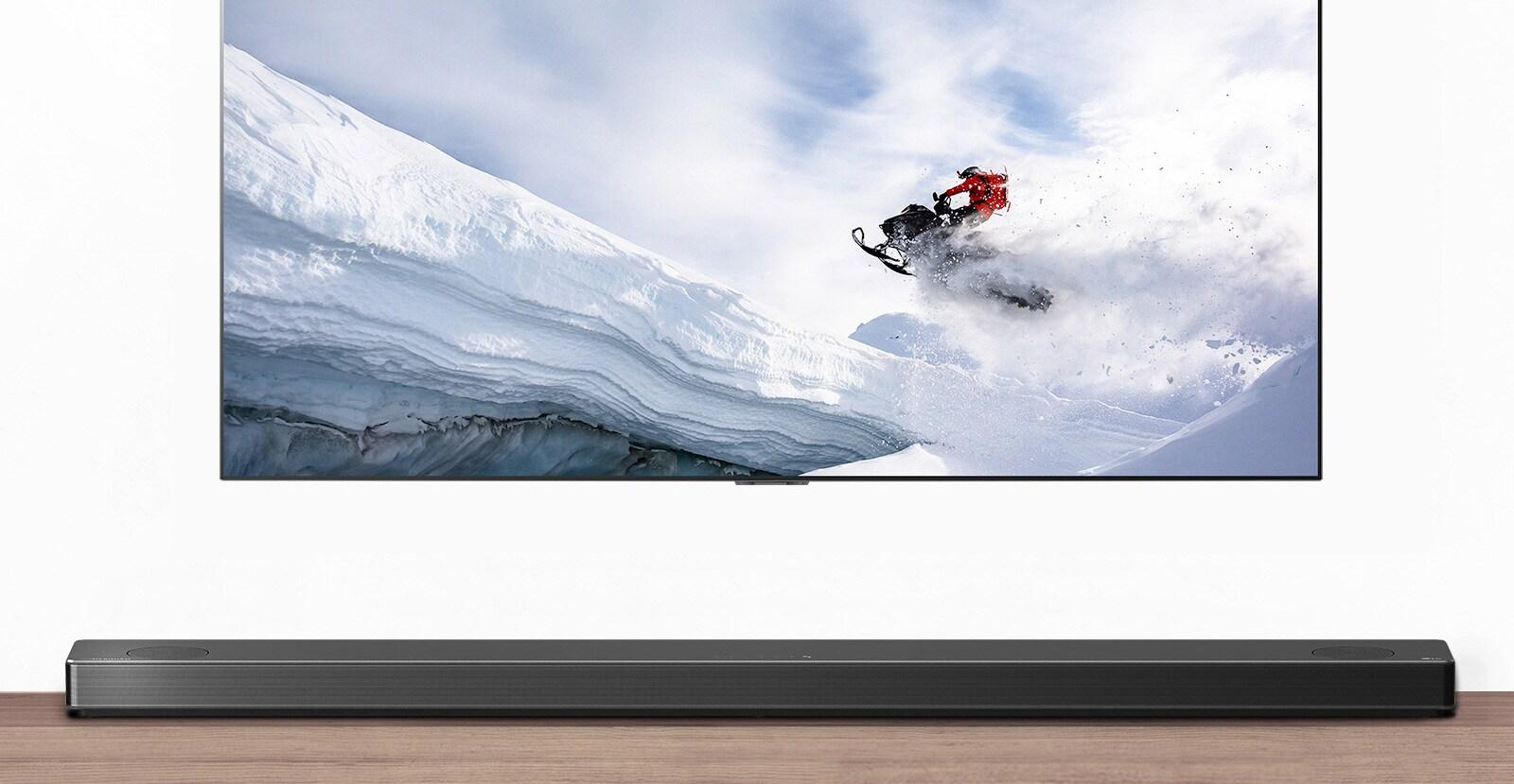 El televisor y la barra de sonido se ven desde la parte frontal. El televisor muestra un hombre pilotando una moto de nieve en las montañas nevadas. El logo HDMI 2.1 está debajo del televisor.