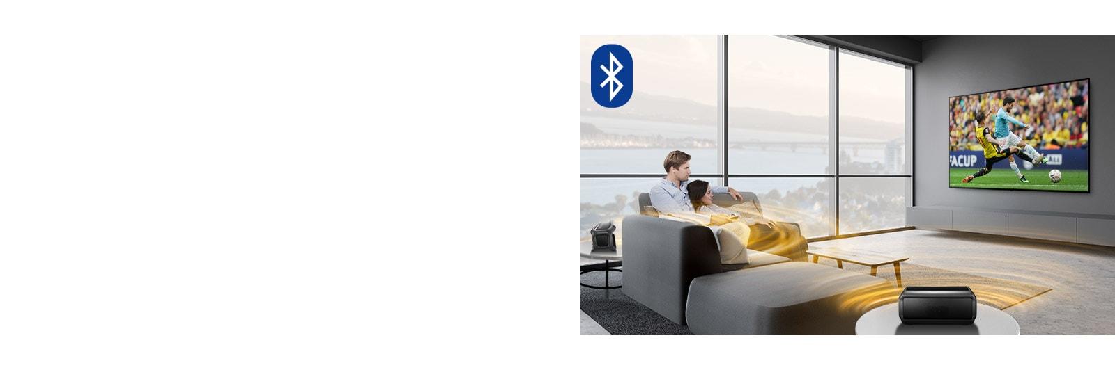 Un hombre y una mujer mirando deporte en el televisor del salón con unos altavoces Bluetooth traseros