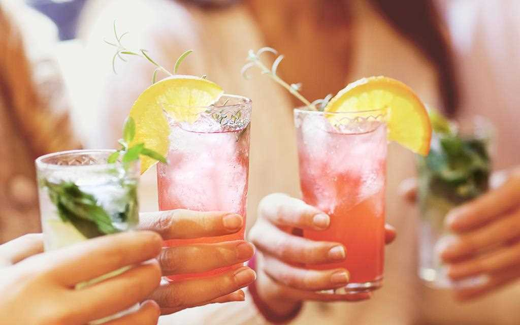 Girls are holding glasses of fruity summer punches.