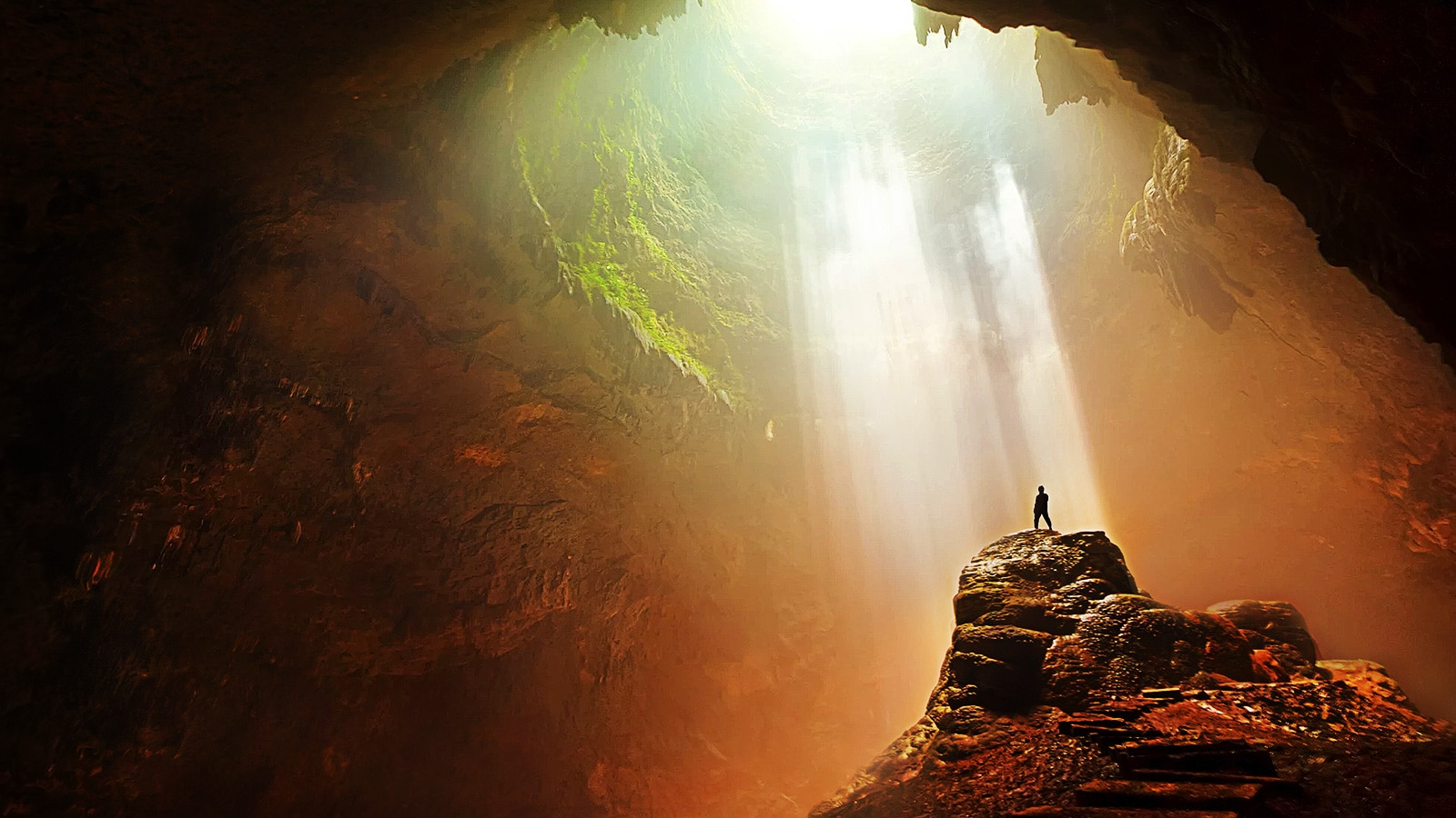 Silhouette dans une grotte avec un puit de lumière
