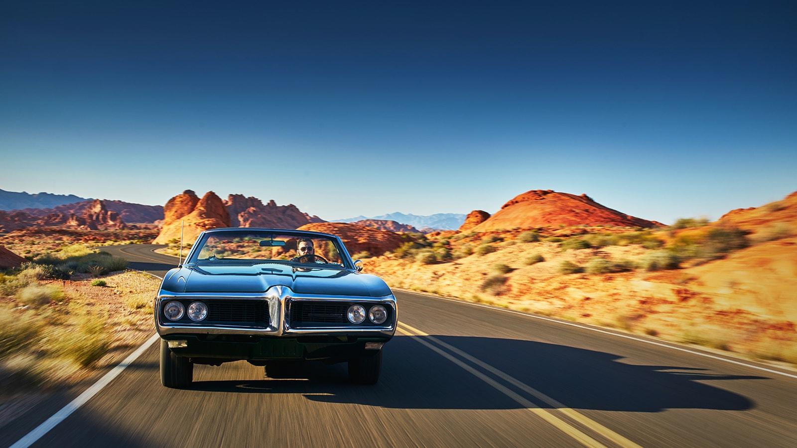 Un homme qui conduit une voiture sur une route de désertique