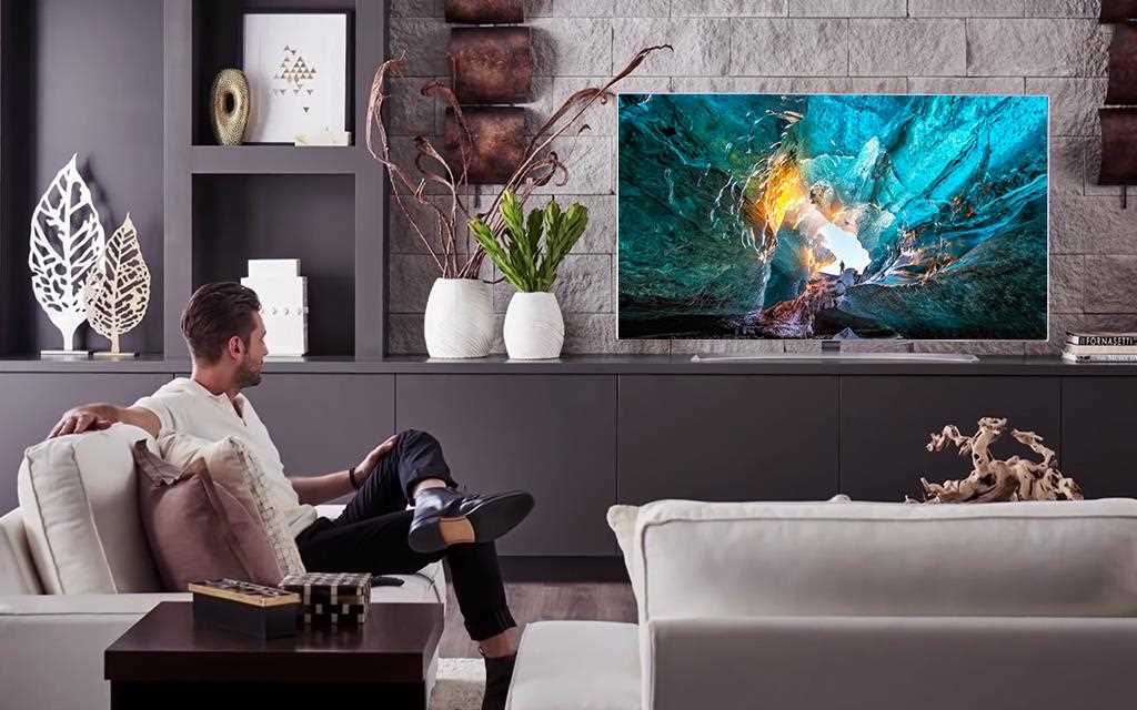 A man and lg signature wallpaper tv w7 in a living room.