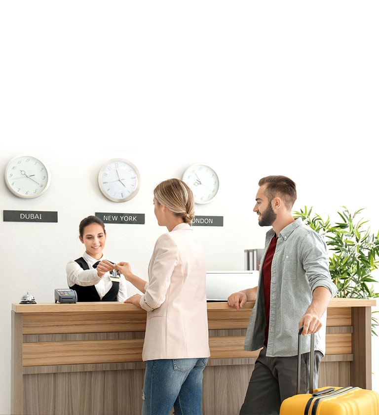 An image of a couple checking in with a receptionist at a hotel lobby.