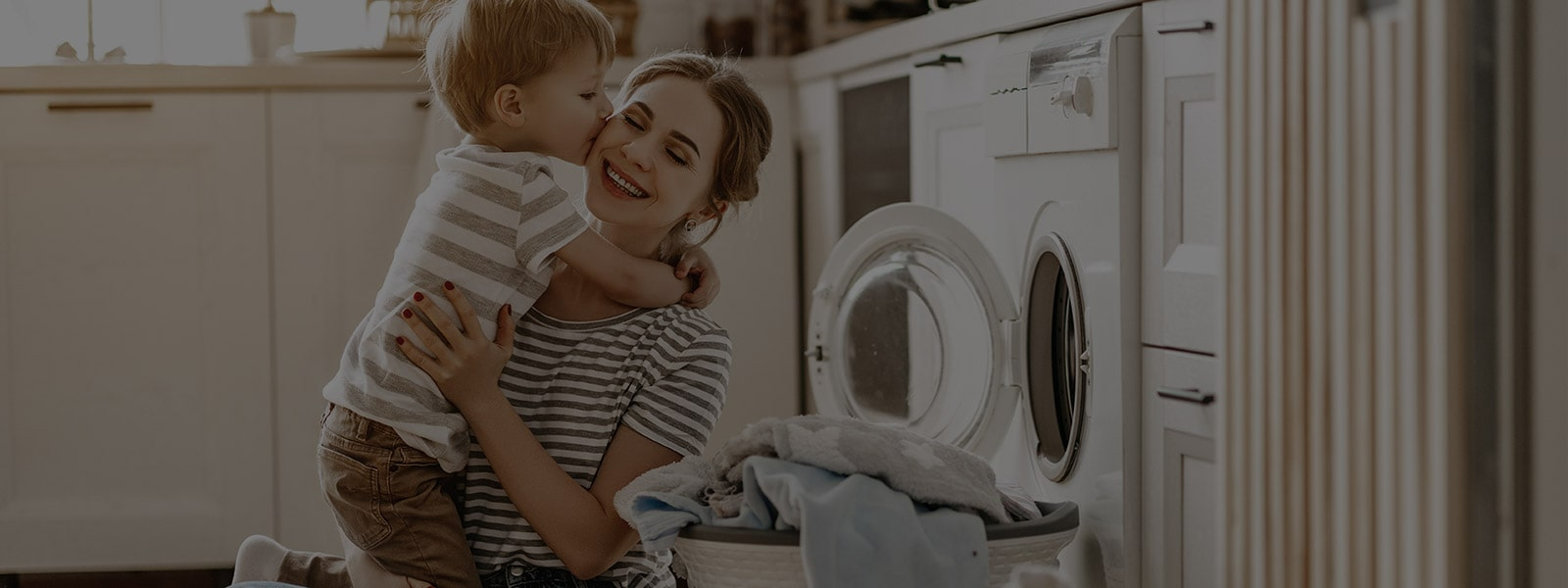 It's an image of a mother and a baby sitting in front of a washing machine.