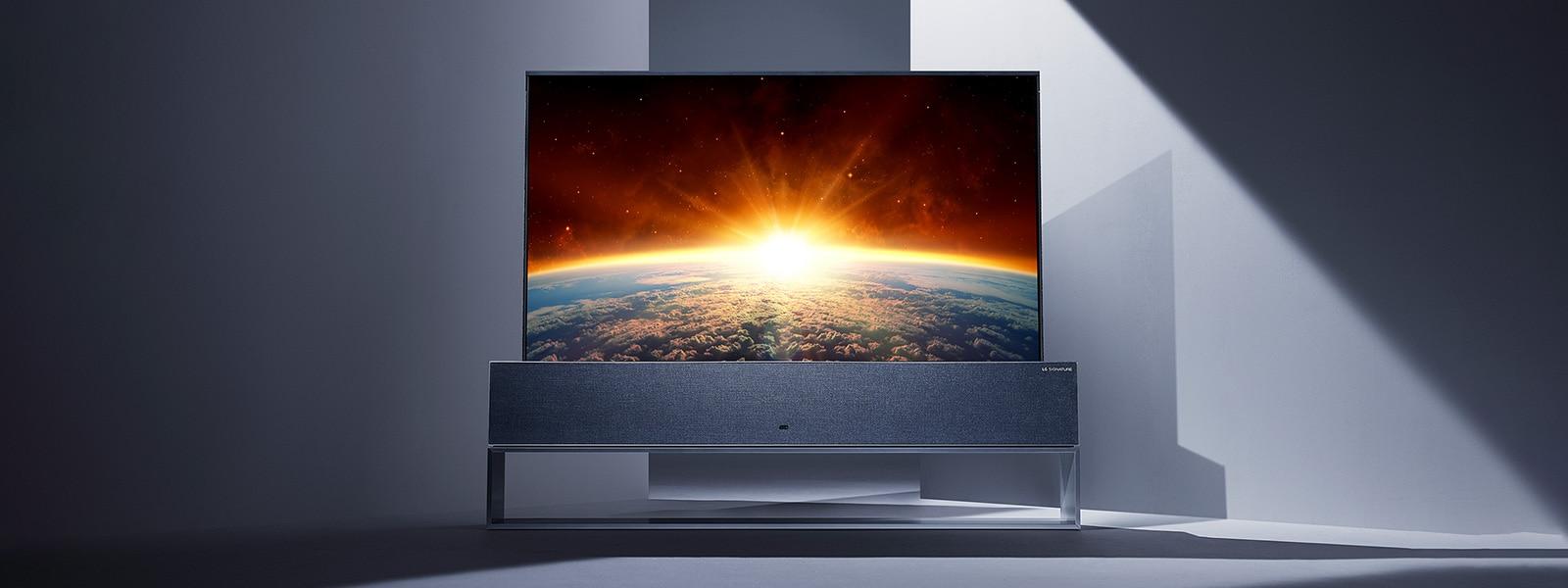 Изображение телевизора на колесиках LG SIGNATURE на колесиках в полный рост в центре серого пространства.