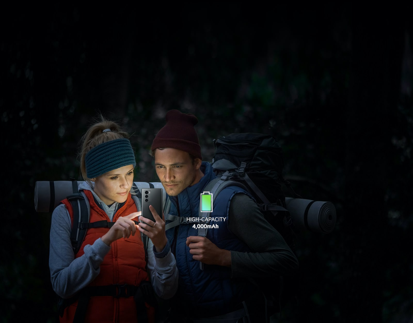 Couple watching a smartphone screen while climbing in the dark night.