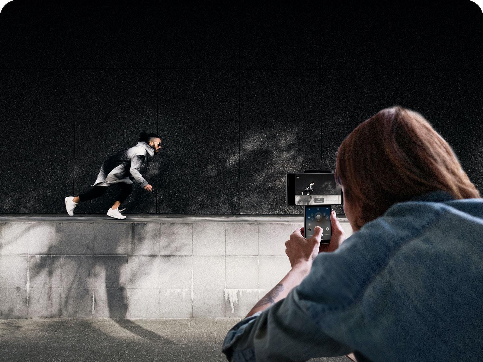 Woman filming a running man.