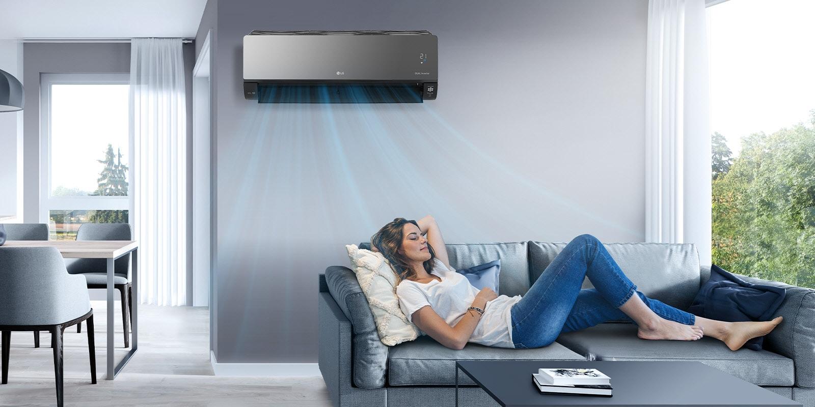Μια γυναίκα περνάει την ώρα της στον καναπέ ενός καθιστικού, με το κλιματιστικό της LG τοποθετημένο στον τοίχο, επάνω από αυτήν. Στην εικόνα φαίνονται μπλε δέσμες αέρα που υποδεικνύουν ότι το κλιματιστικό είναι ενεργοποιημένο και ψύχει τον χώρο.