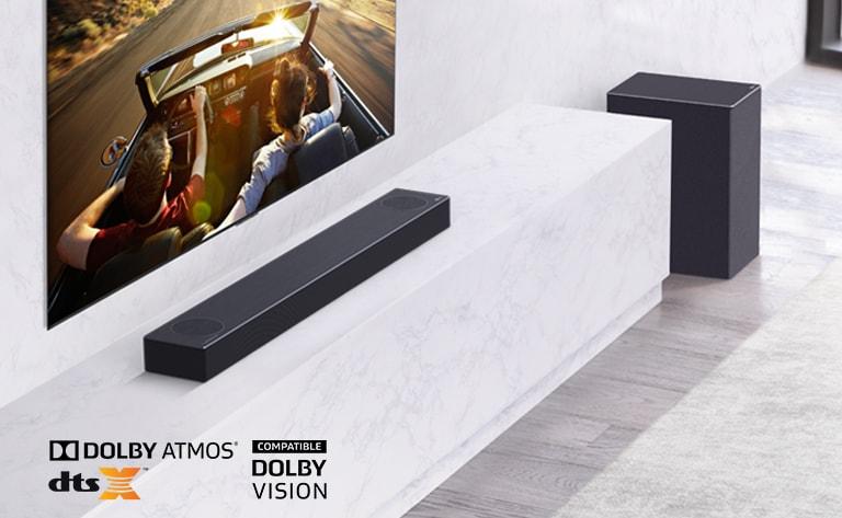 Η τηλεόραση είναι τοποθετημένη στον τοίχο και το LG Soundbar βρίσκεται κάτω από ένα λευκό μαρμάρινο ράφι, με ένα subwoofer στα δεξιά. Η τηλεόραση δείχνει ένα ζευγάρι μέσα σε ένα αυτοκίνητο.