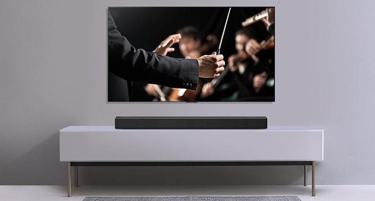 Απεικόνιση μιας τηλεόρασης σε γκρίζο τοίχο, με ένα LG Soundbar τοποθετημένο σε ένα γκρίζο ράφι, από κάτω της. Η τηλεόραση δείχνει έναν μαέστρο που διευθύνει μια ορχήστρα