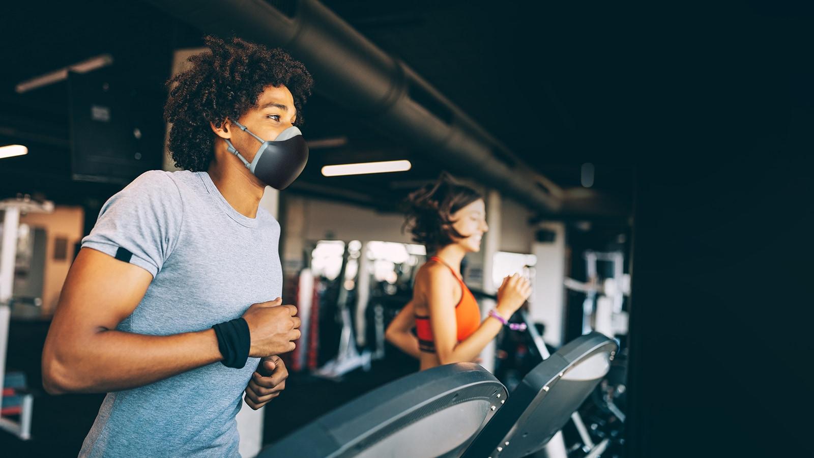一名戴著黑色 LG PuriCare 穿戴式空氣清新機的非裔美國男子正在健身室的跑步機上跑步。他看起來呼吸順暢,神態自若。