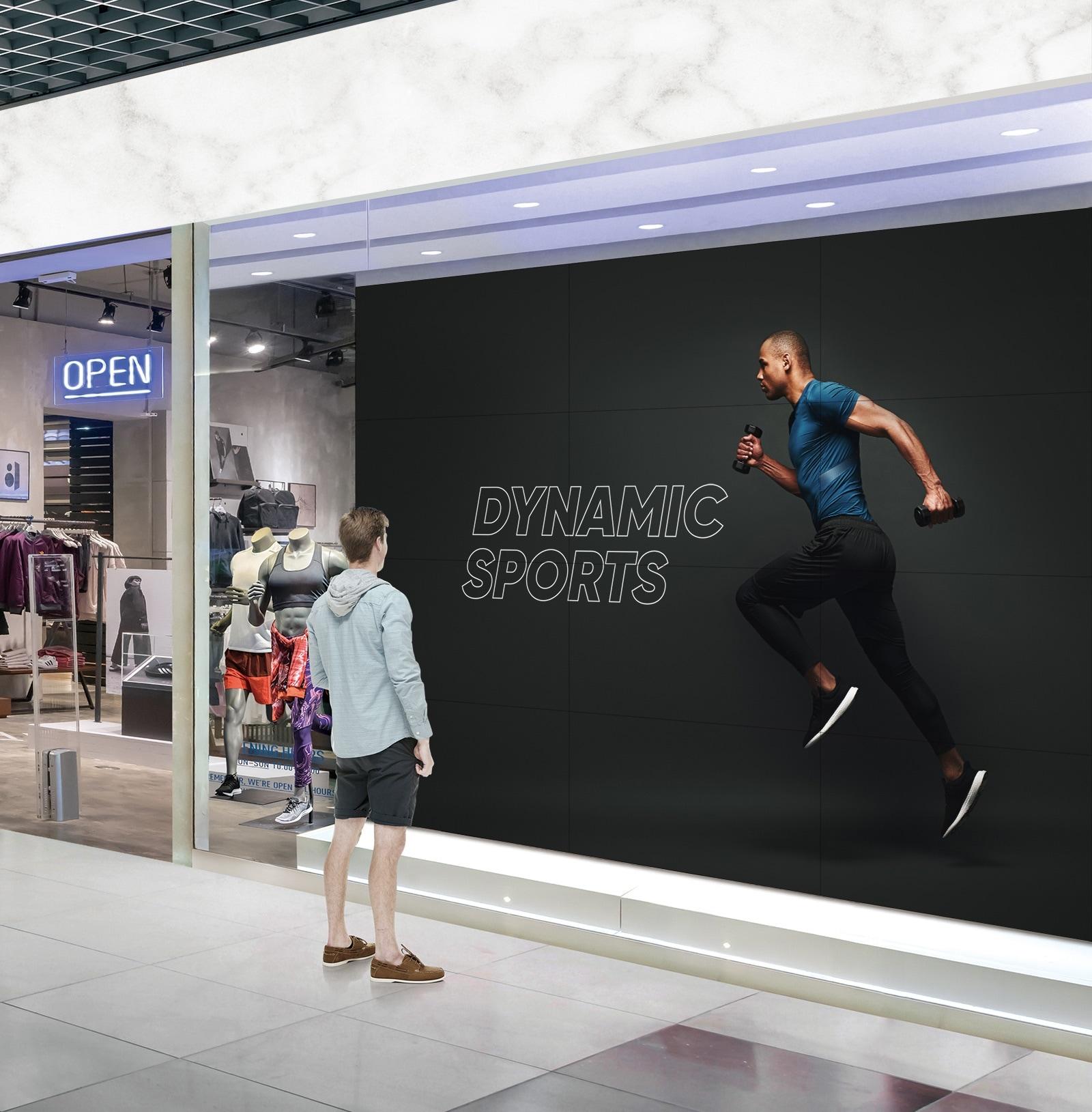 Un hombre está mirando una pantalla grande pegada al escaparate de una tienda de deportes.