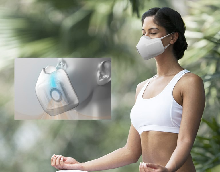 A woman sits in a forest with the Puricare Wearable Air Purifier on as she does yoga. A video inset in the image shows a computer generated version of the Wearable Air Purifier and magnifies into the interior of the Wearable Air Purifier to show how the air goes and out of the Wearable Air Purifier.
