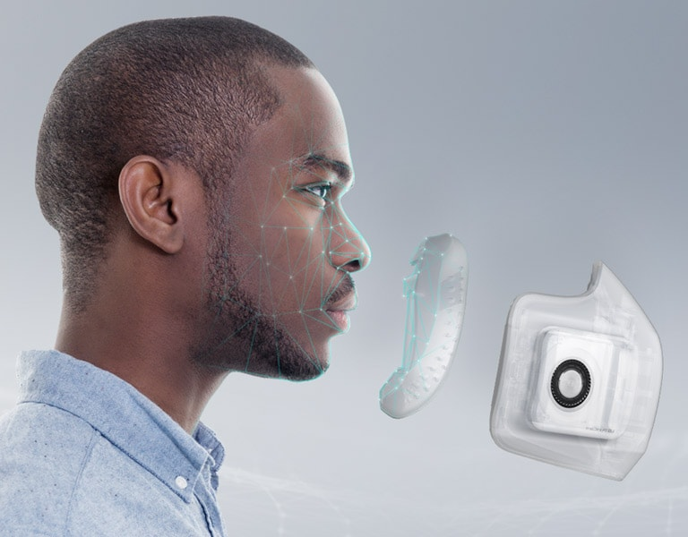 The side of a man's face is shown with dots and lines mapped on to his face. In front of his face is the interior part of the Wearable Air Purifier and then the exterior Wearable Air Purifier indicating that it fits comfortably and seals to his face.