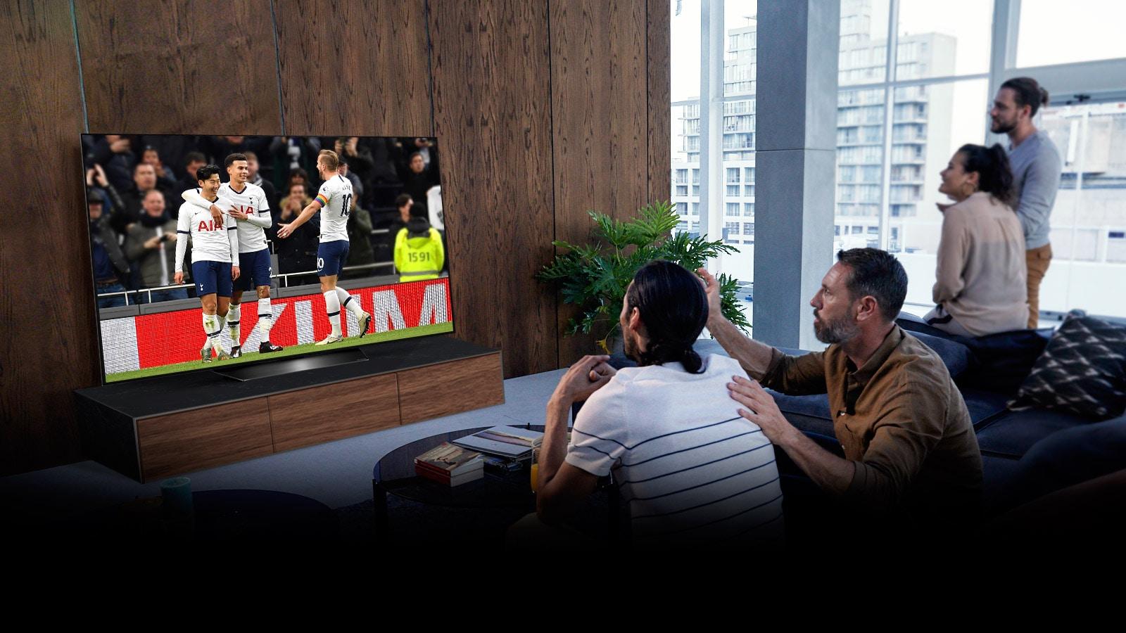 Ljudje, ki gledajo tekmo Tottenhama po televiziji v dnevni sobi