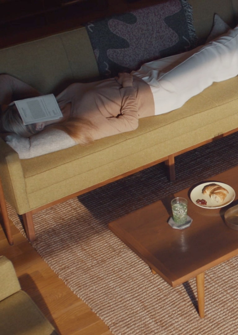 A video opens with a hand falls off the side of a couch and the shadows move across it. The shot moves out to show a woman laying on a couch taking a nap. Switch to a shot of the LG Dual Inverter air conditioner as it turns on. Video then  switches to the LG air purifier turning on across the room. Next the video shows a kitchen and zooms out from a focus on the LG dishwasher to the entire kitchen. The next shot shows an LG robot vacuum cleaner as it moves across the living room floor. The next shot shows the LG stove and oven installed in the kitchen and then the video shows the side angle of the LG Instaview refrigerator. The video switches to see the LG washer and dryer running. Next, a hand holds a phone with the LG ThinQ app open and a thumb hits the button to turn off the oven. Next a woman can be seen laying down talking into an AI speaker. The shot switches to a TV and in the upper right corner a message pops up to let the viewer know the refrigerator door has been left open. The video ends with the same woman sleeping on a bed with cereal scattered around her and on the floor and the robot vacuum comes into view to clean up.