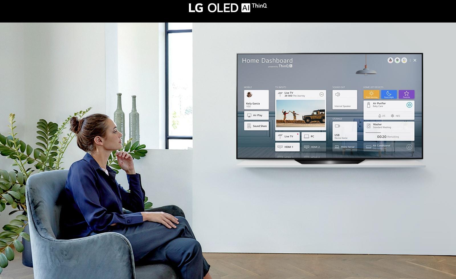 Žena sjedi na naslonjaču u dnevnoj sobi, a na zaslonu televizora prikazuje se kućna nadzorna ploča (Home Dashboard)