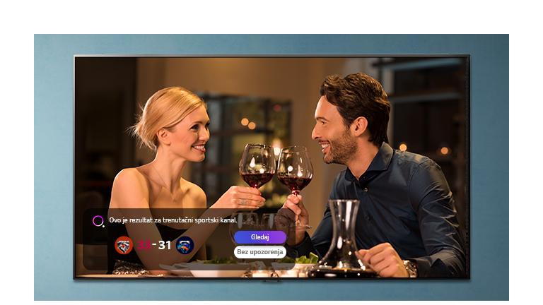 Muškarac i žena nazdravljaju čašama na TV zaslonu dok dolaze obavijesti o sportskim podsjetnicima
