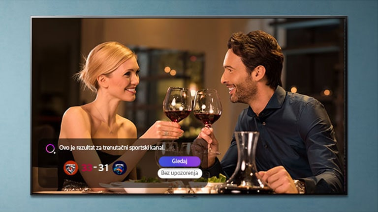 Muškarac i žena nazdravljaju čašama naTV zaslonu dok dolaze obavijesti o sportskim podsjetnicima