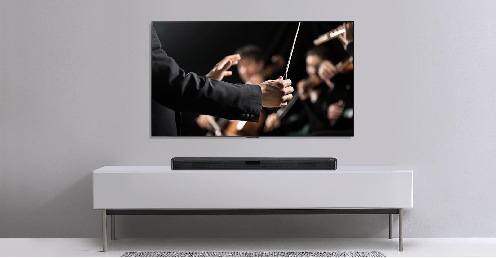 Na sivom zidu nalazi se televizor, a ispod njega na sivoj polici zvučnik LG Sound Bar. Na televizoru je prikazan dirigent koji dirigira orkestrom.