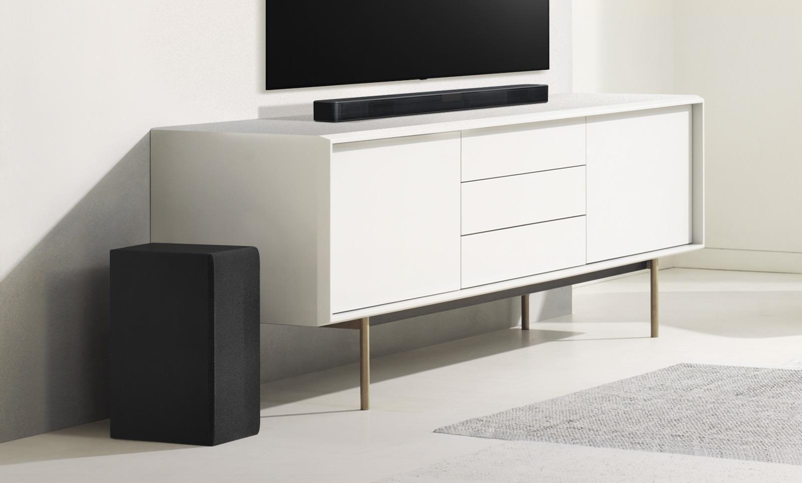 Zvučnik Sound Bar nalazi se na bijeloj polici, a njemu slijeva je niskofrekvencijski zvučnik. Niskofrekvencijski zvučnik doima se većim jer je postavljen više prema naprijed.