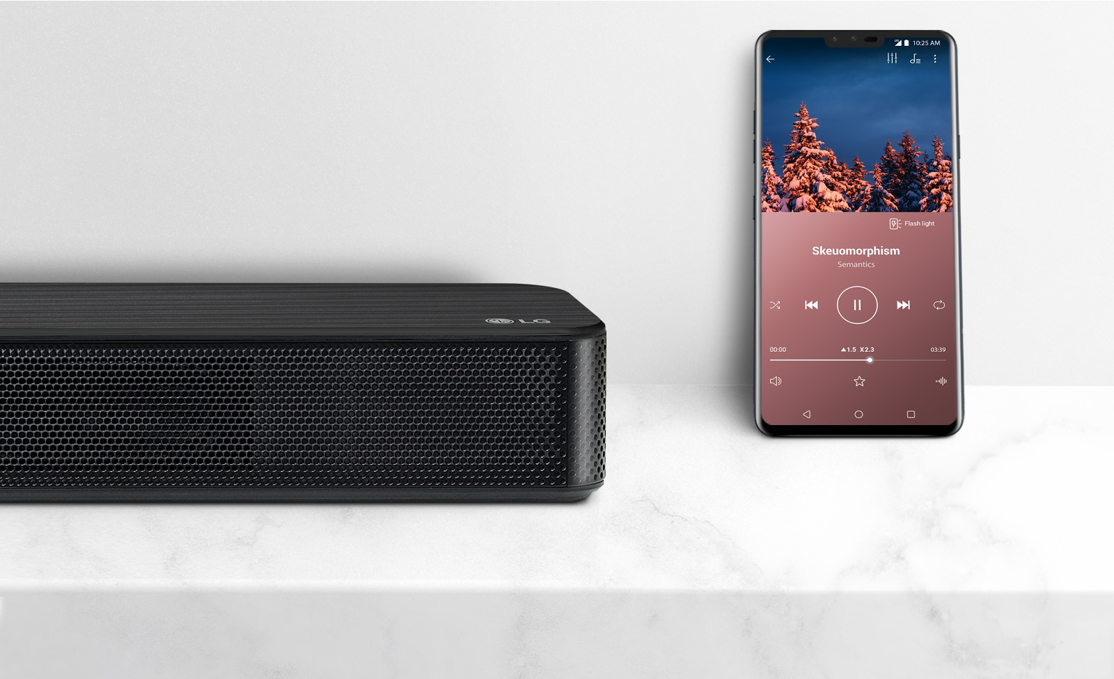 Prikaz izbliza desne strane zvučnika LG Sound Bar u blizini pametnog telefona. Dva se uređaja nalaze na bijeloj polici.