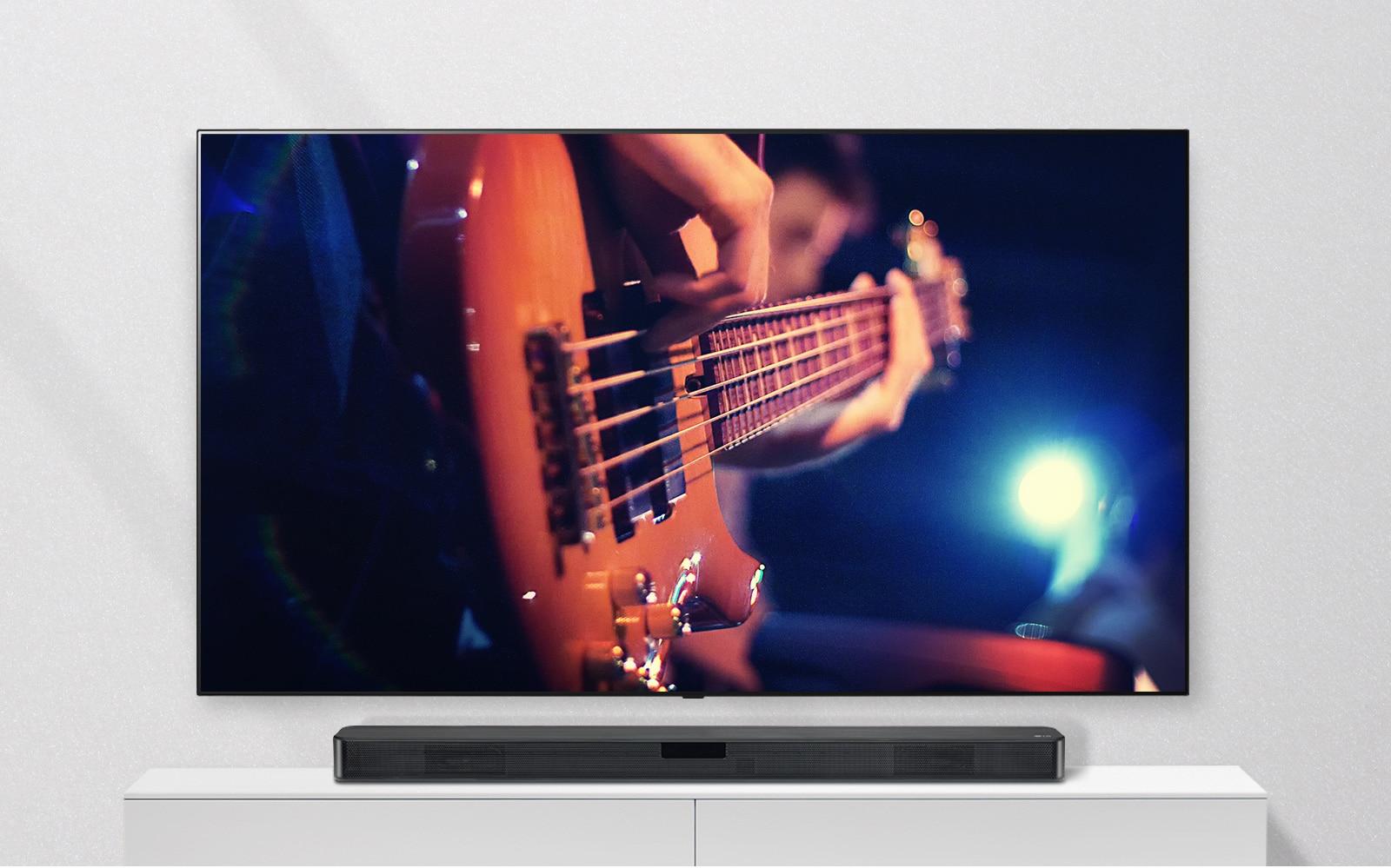 Televizor je pričvršćen na zid, a zvučnik Sound Bar je na bijeloj polici. Na televizoru je prikazan čovjek koji svira gitaru.