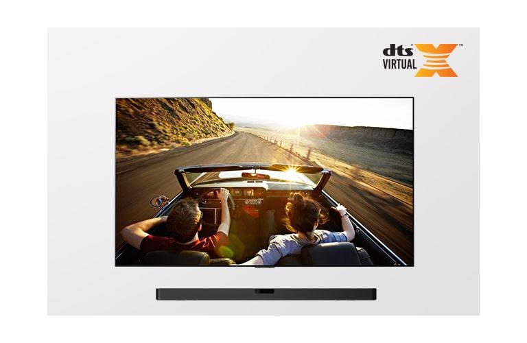 Televizor i zvučnik Sound Bar zajedno u potpunom prikazu. Na televizoru je prikazan par koji se vozi u kabrioletu u suton.