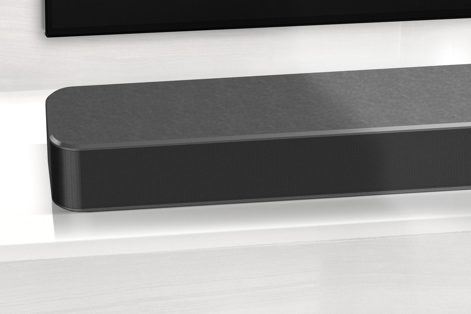Prikaz izbliza zvučnika LG Sound Bar iz lijevog kuta. Vidljiva je i donja lijeva strana televizora.