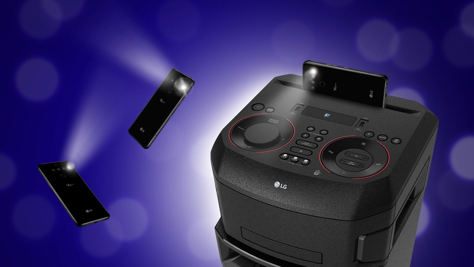 Pogled od blizu na vrh sistema LG XBOOM. Okoli njega sta dva pametna telefona z utripajočimi lučmi.
