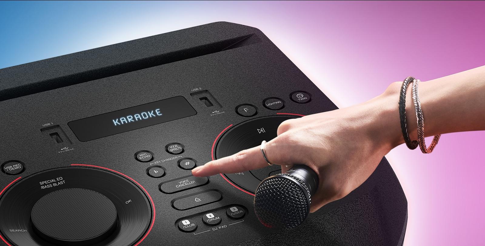 Roka, ki drži mikrofon, poskuša pritisniti gumb Voice Canceller na vrhu sistema LG XBOOM.