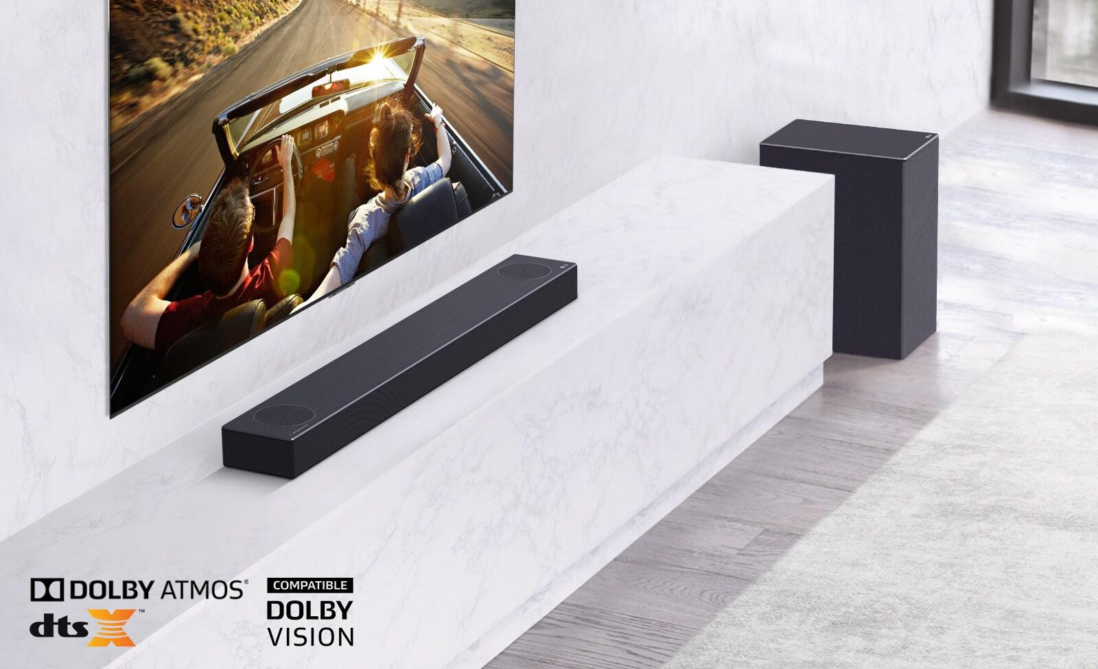 Televizor je na steni, zvočnik LG Soundbar je pod njim na polici iz belega marmorja, desno od njega pa je nizkofrekvenčni zvočnik. Televizija prikazuje par v avtu.