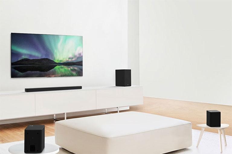 Zvok za televizor in zvočnik v beli dnevni sobi z belim kavčem v središču sobe. Zvočniki so nameščeni na obeh straneh kavča.